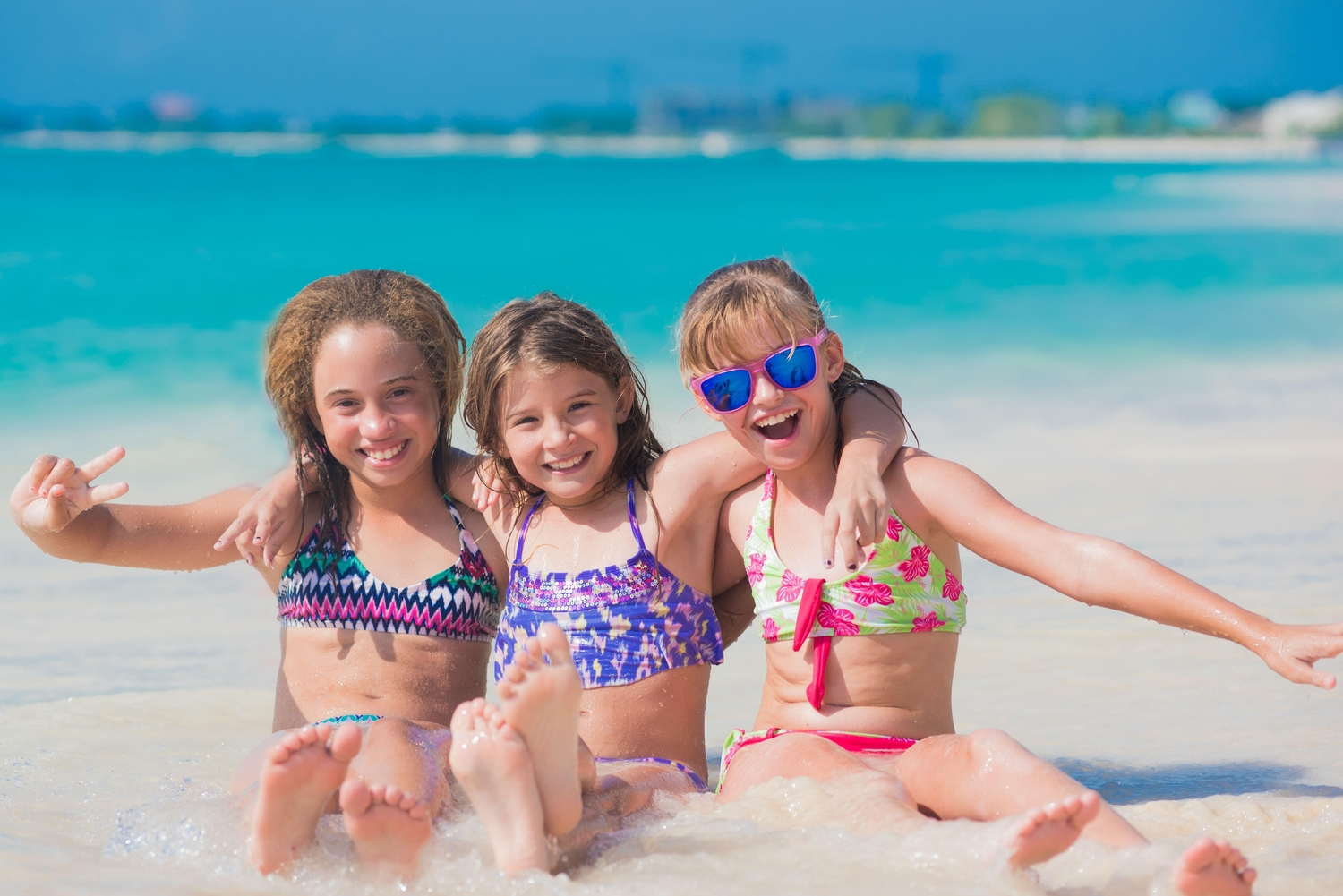 3 young girls sitting in shallow water on Seven Mile Beach