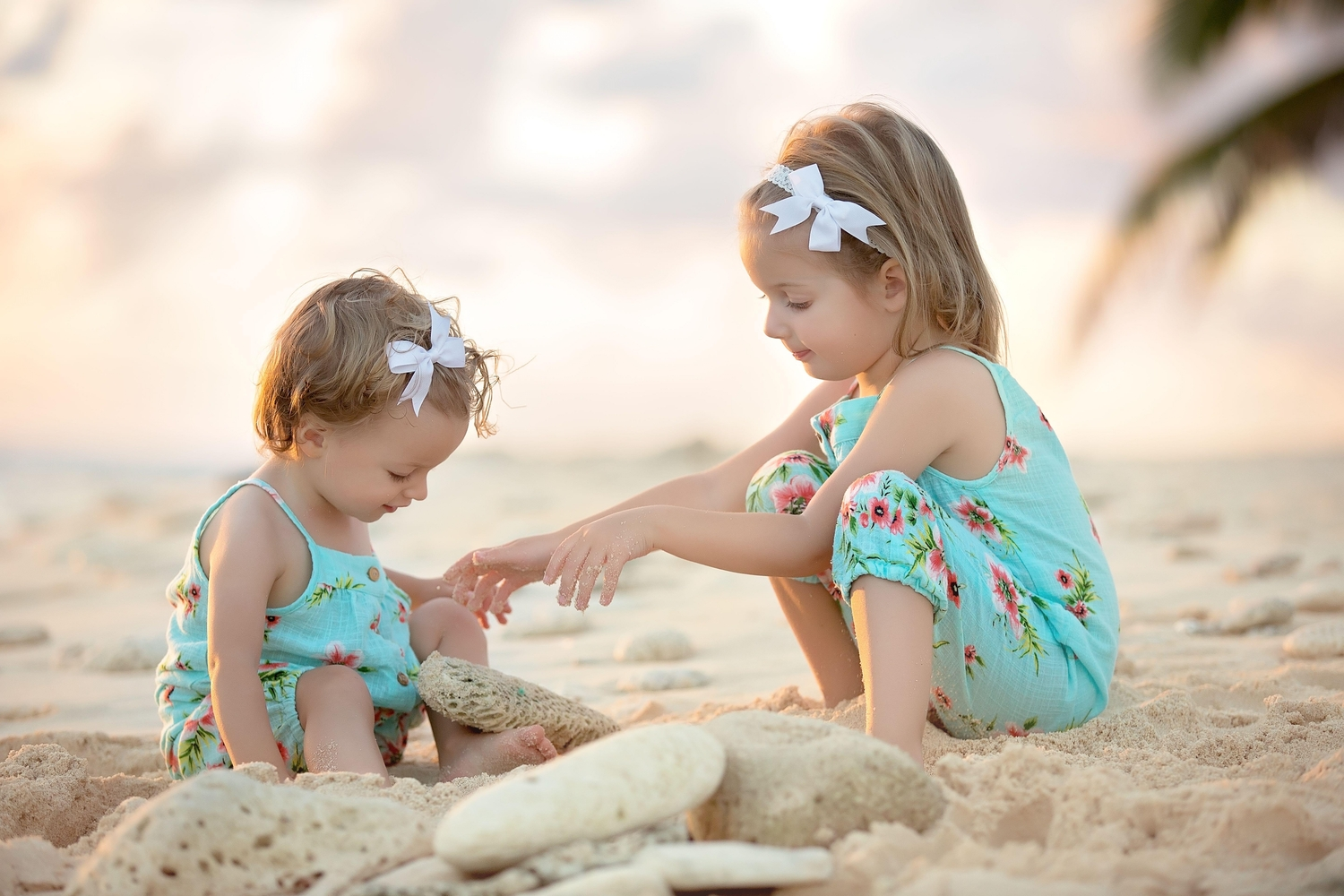 Baby and her young sister playing in the sand on the beach