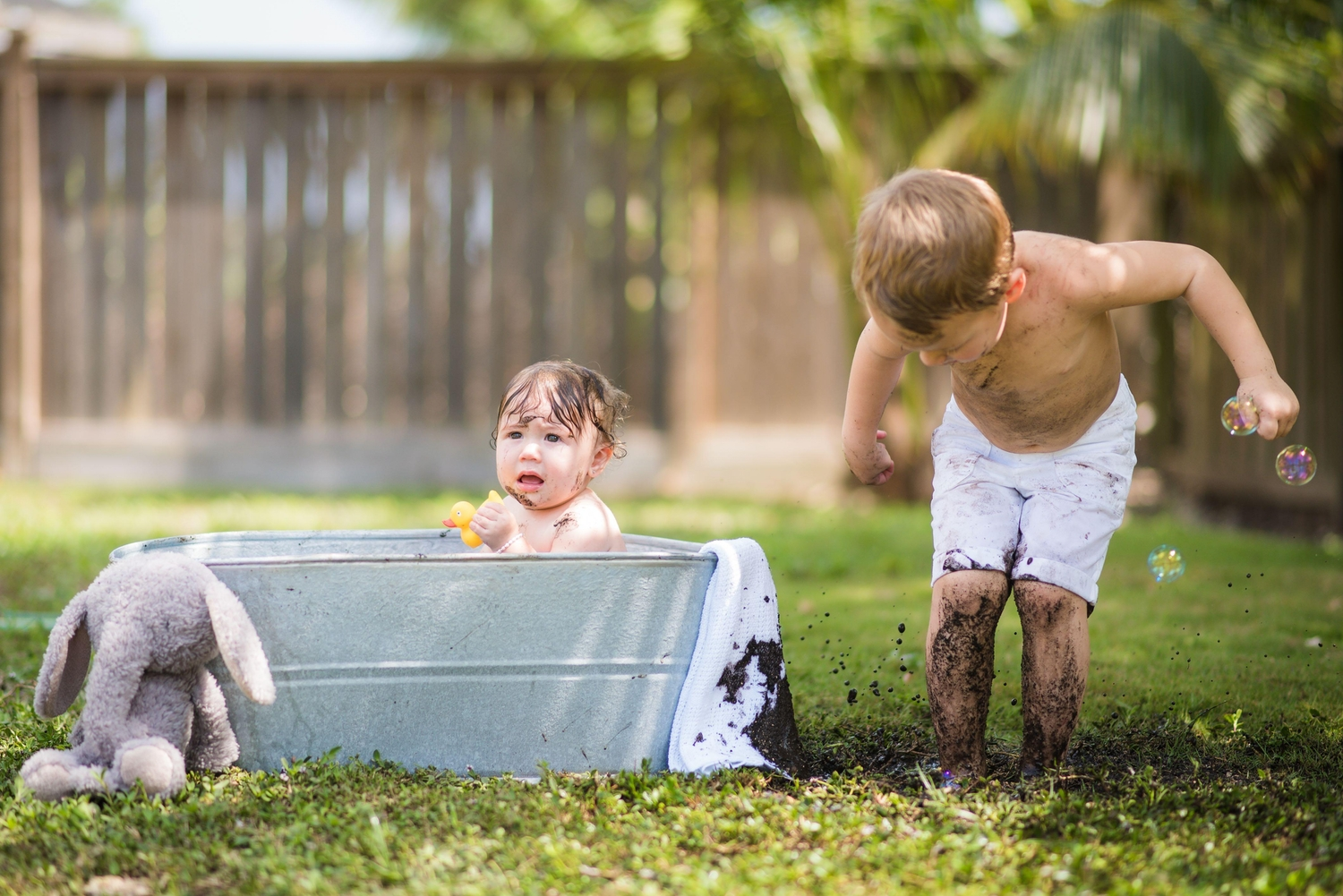 Baby taking a bath in metal tub with brother playing in the mud next to him