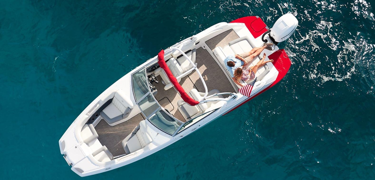 Aerial shot of a couple relaxing on a floating speed boat