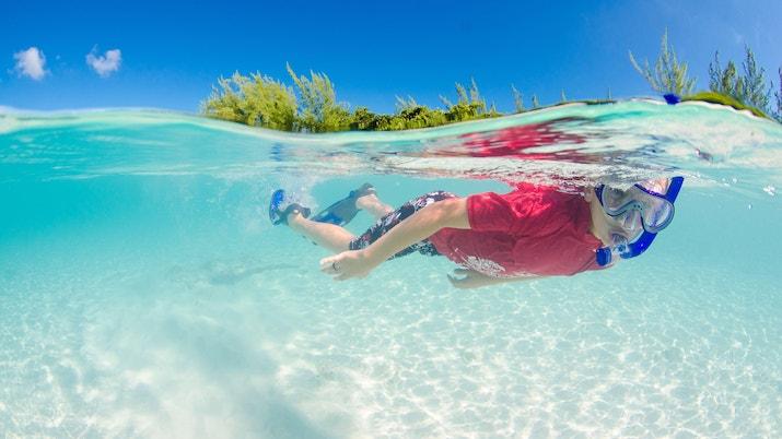 Boy snorkeling in clear water in the Cayman Islands
