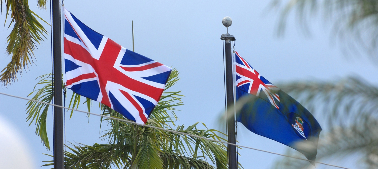 Cayman Islands and Union Jack flag on poles in between palm trees on the Cayman Islands