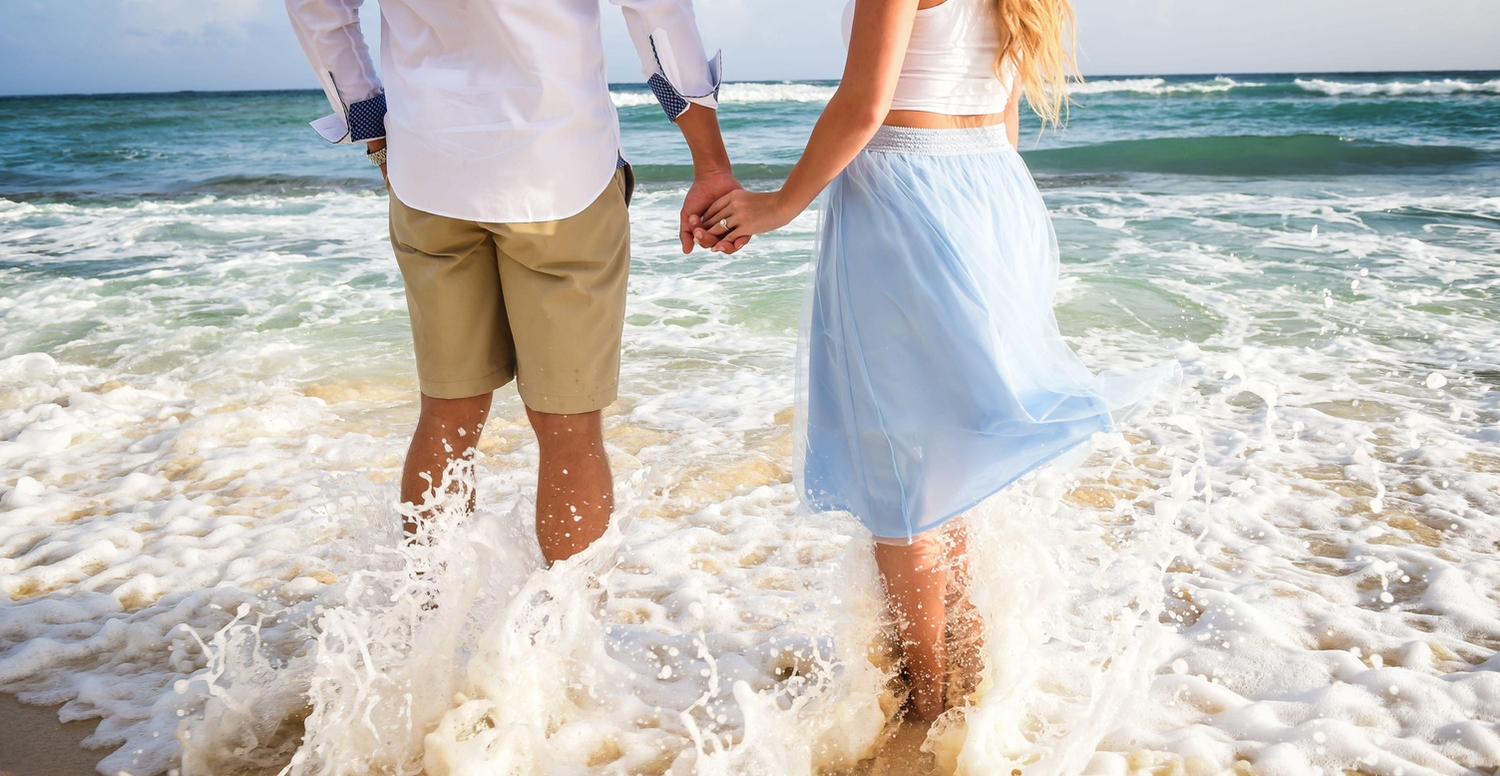 Couple holding hands while wading through the water on the beach