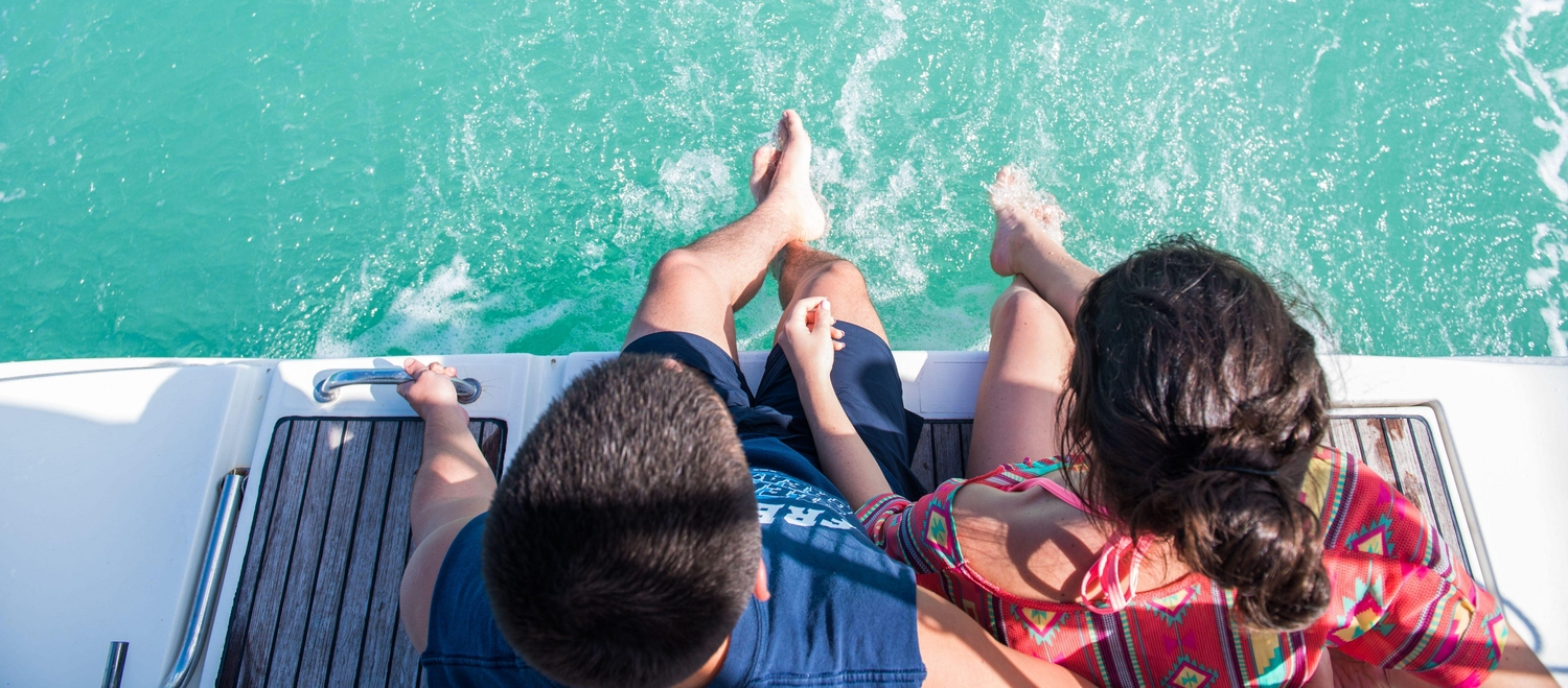 Couple sitting with feet hanging in the water off the edge of a boat