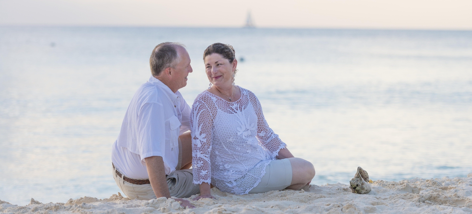 Elderly couple staring into each others eyes while sitting on the beach