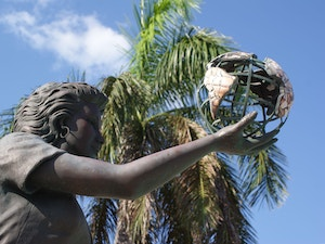 Female statue holding a metal earth at Heroes Square in the Cayman Islands