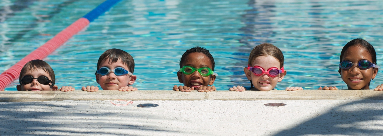 Five kids looking over the edge of large swimming pool