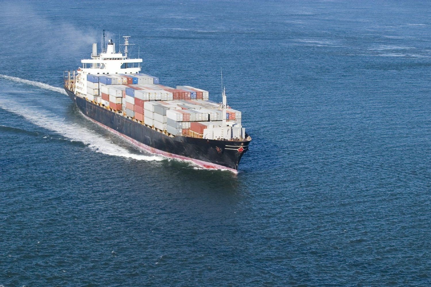 Full container ship transporting cargo in the ocean