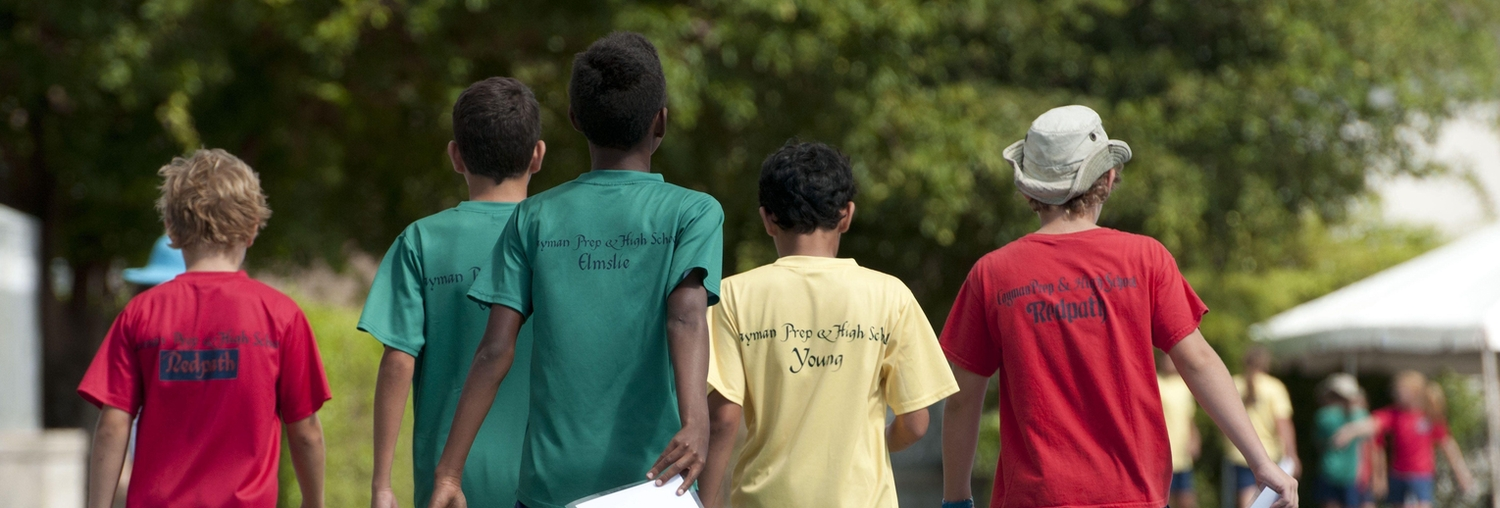Group of young boys walking next to an athletics track
