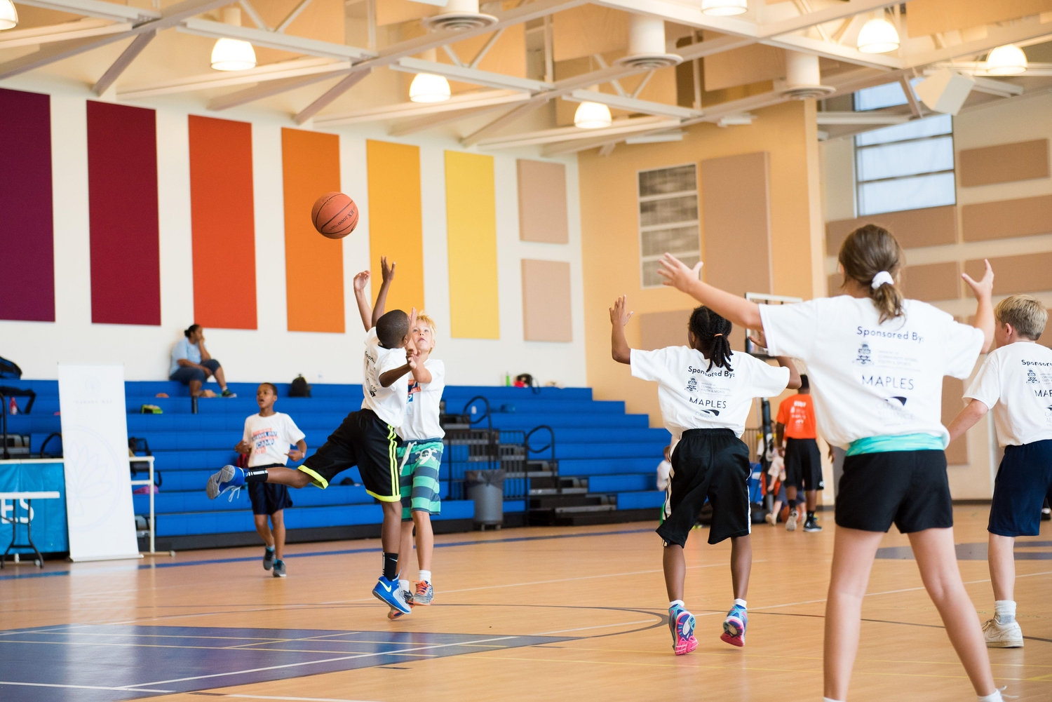 Kids playing basketball at an indoor sports facility