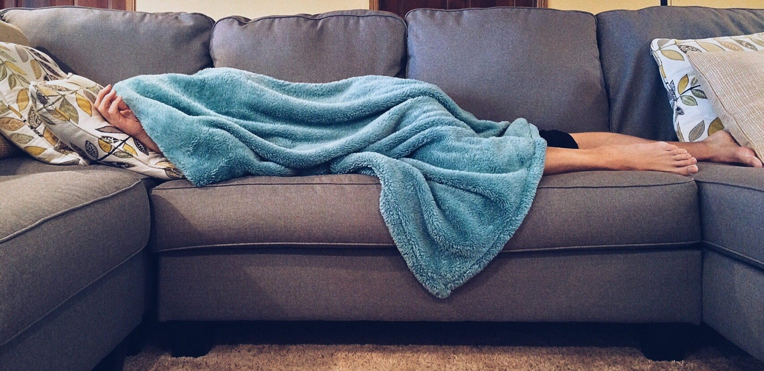 Lady on couch under blanket sick with Dengue