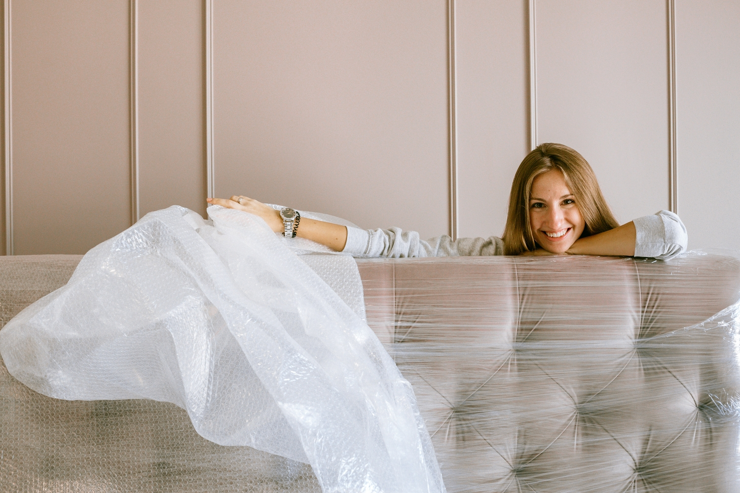 Lady unwrapping plastic off couch after moving