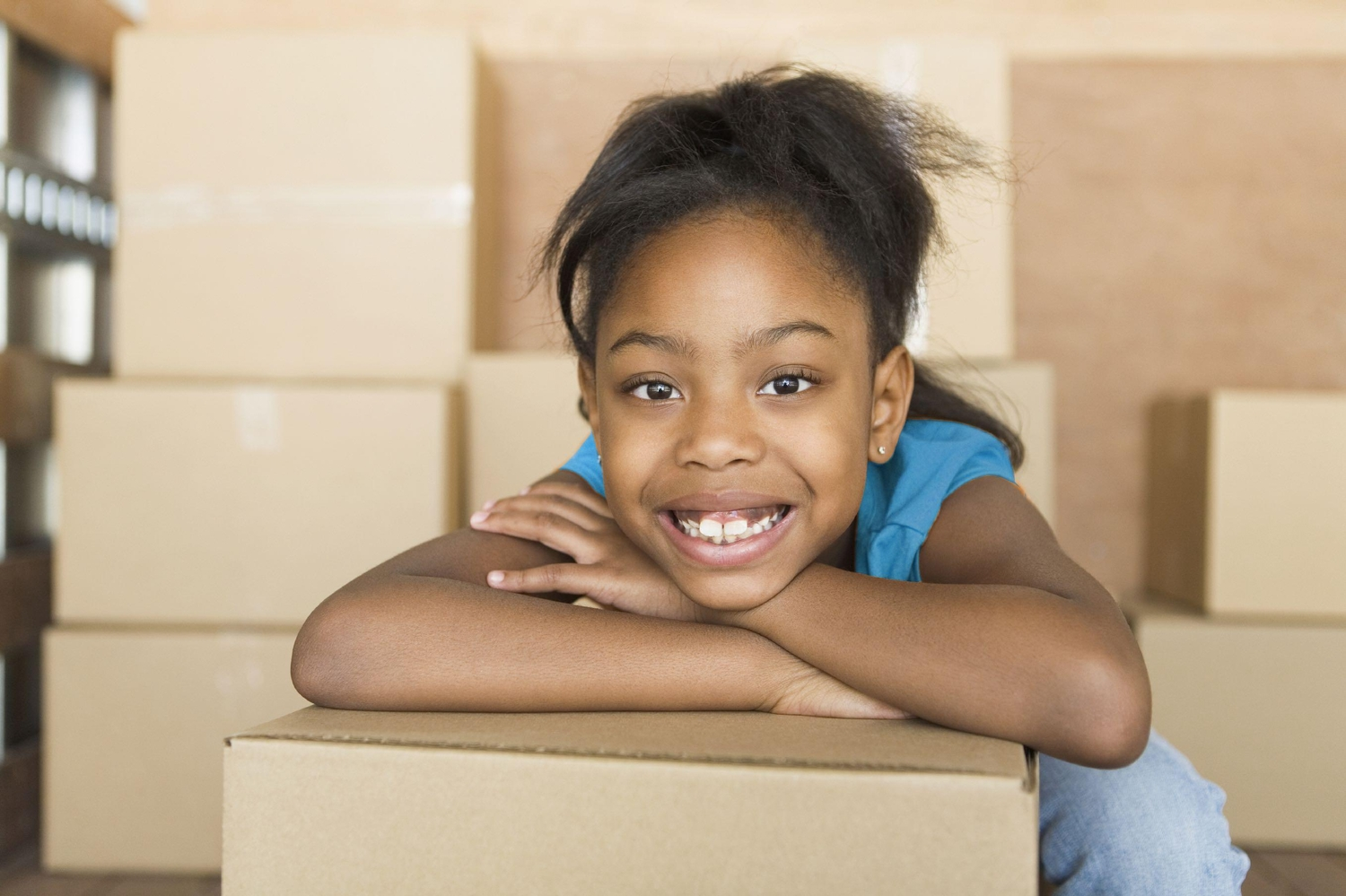Young girl smiling and leaning on moving box in a room full of boxes