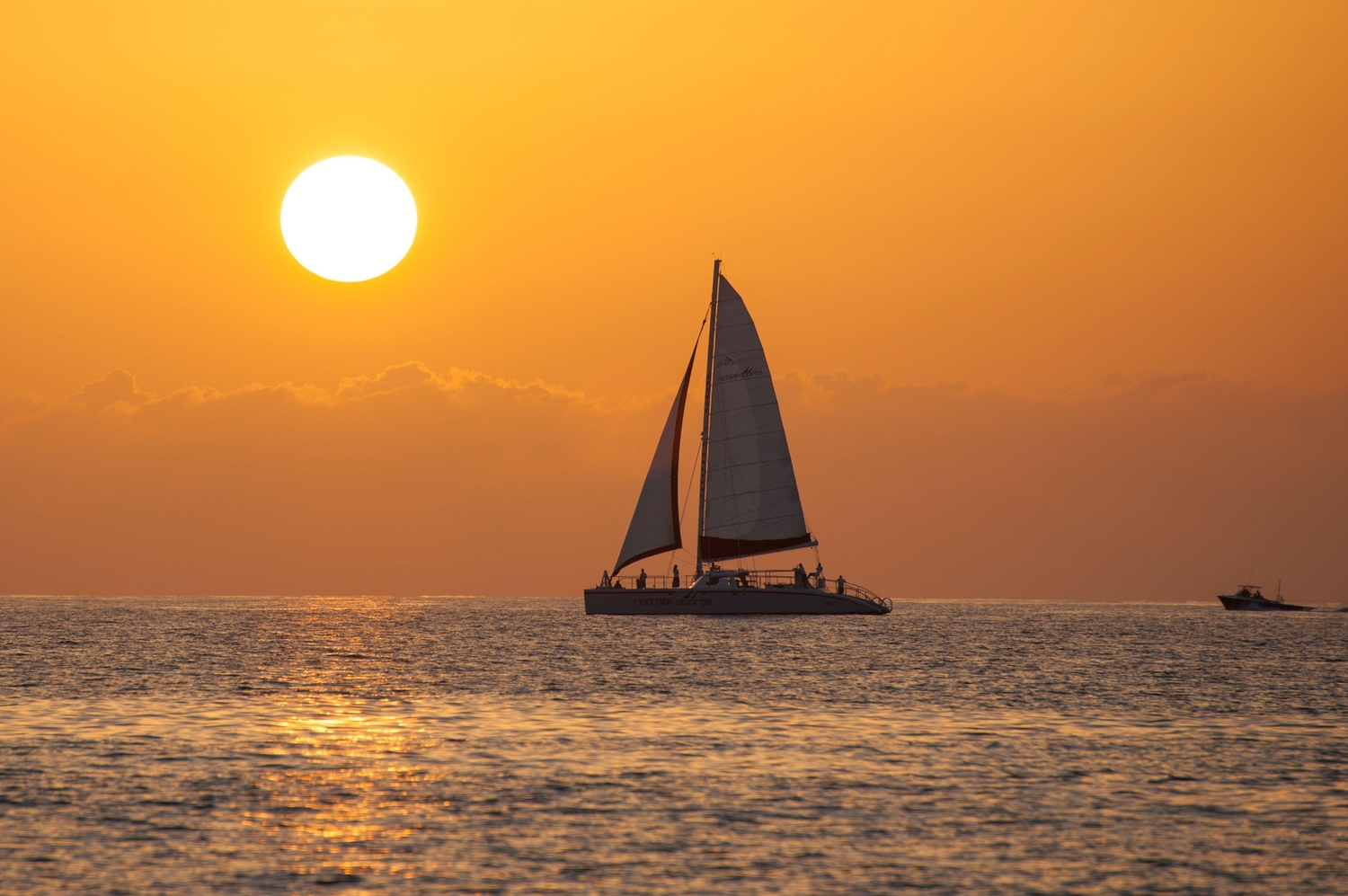 Sailing boat on out at sea during sunset
