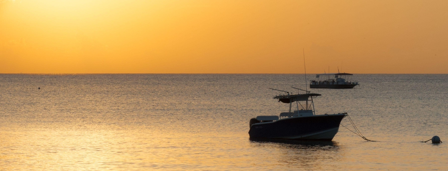 Small fishing boat anchored offshore during sunset