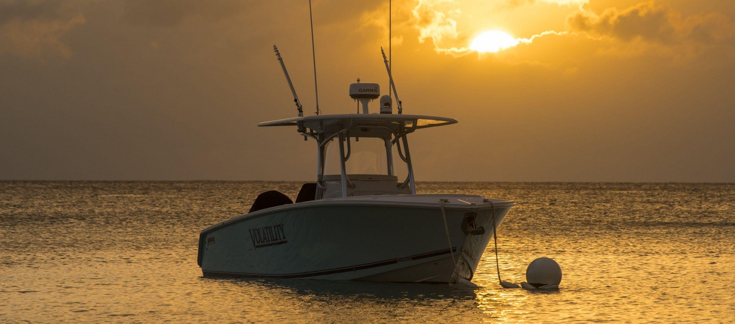 Speed boat anchored offshore during sunset