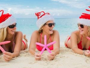Three ladies laying on the beach wearing Santa hats and holding fake starfish
