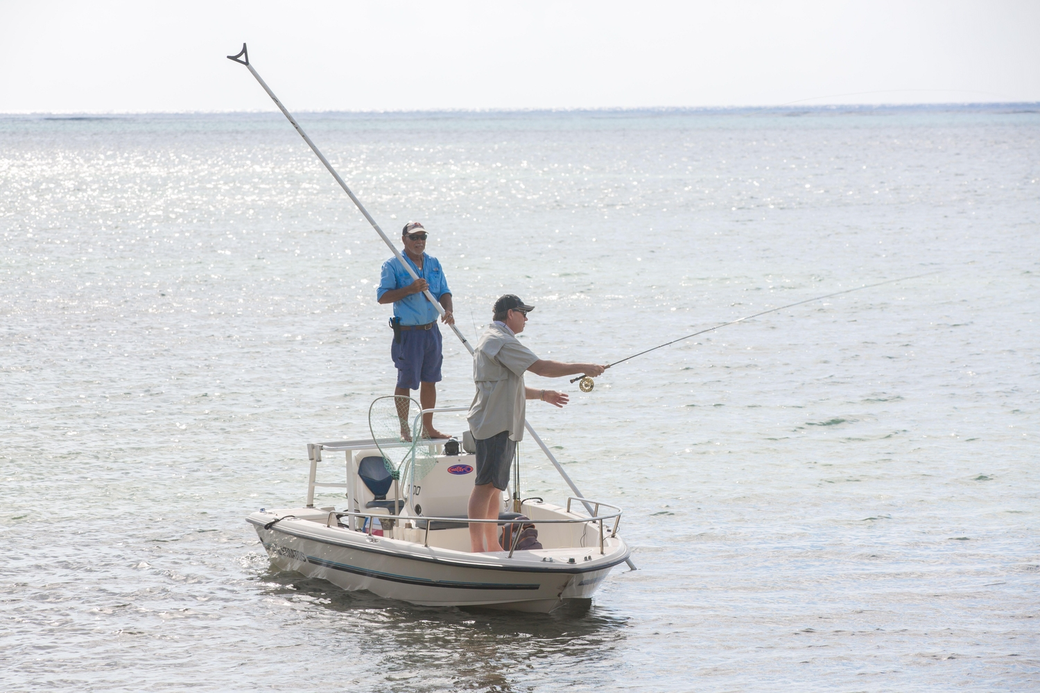 Two men fly fishing off small boat