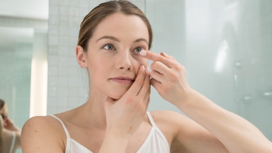 Woman Holding contact lens to eye looking in mirror