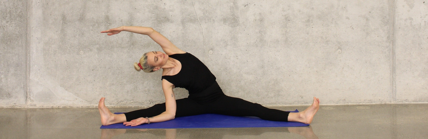 Woman wearing all black against gray wall doing seated side stretch