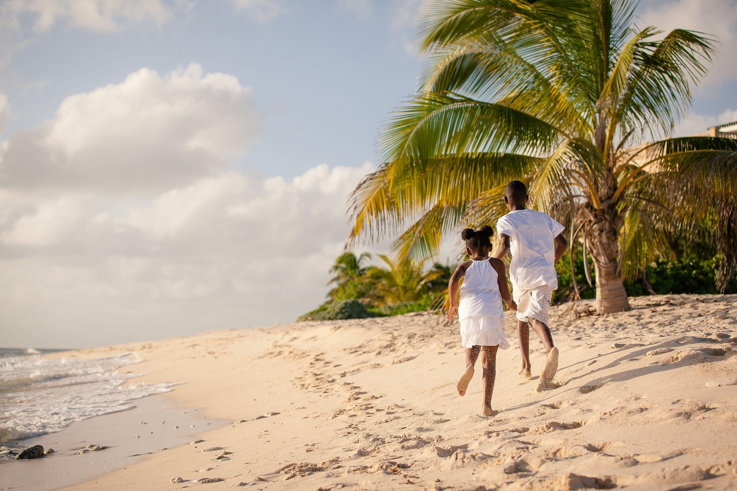 Young girl and boy dressed in white running on the beach