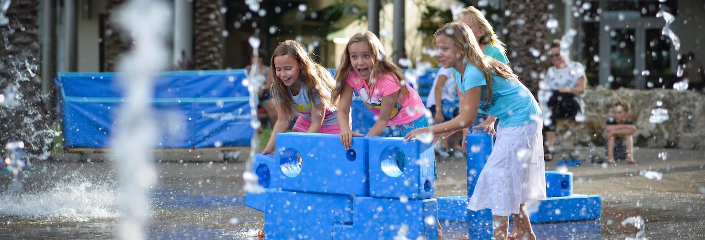 Young girls playing near a water fountain