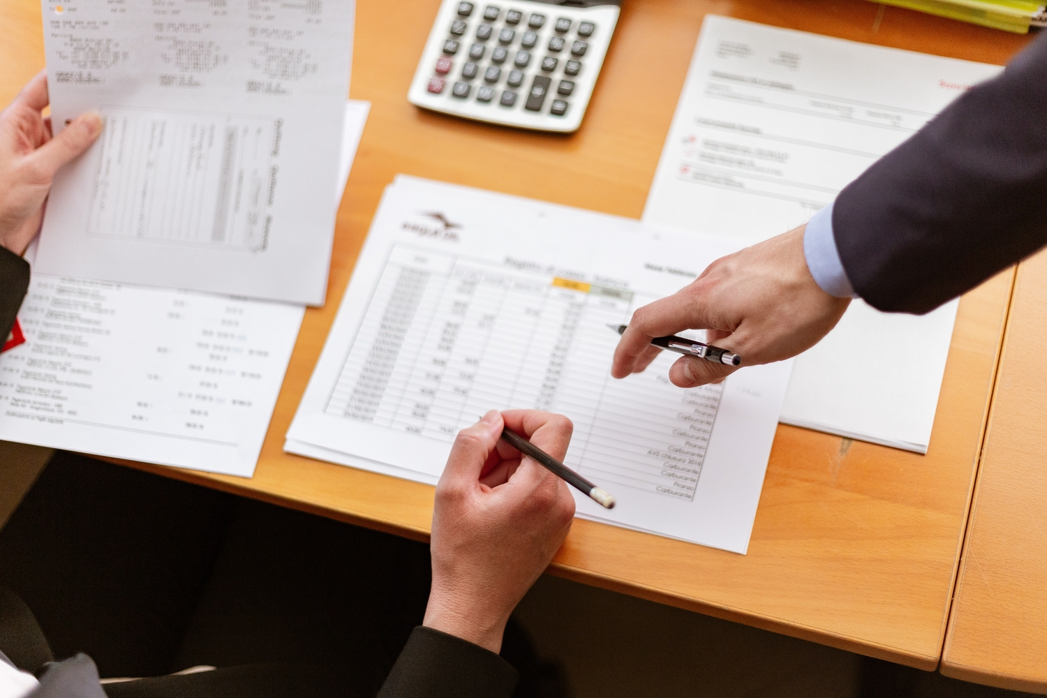Accountant resting their hand on table with calculator and papers