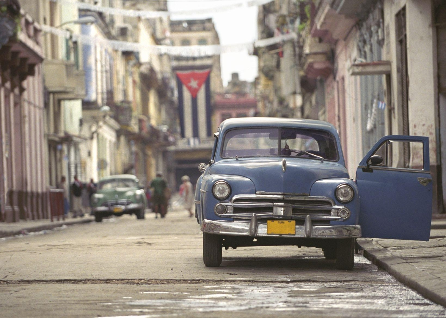 An old blue car parked on an empty street in havana with the cuban flag hanging