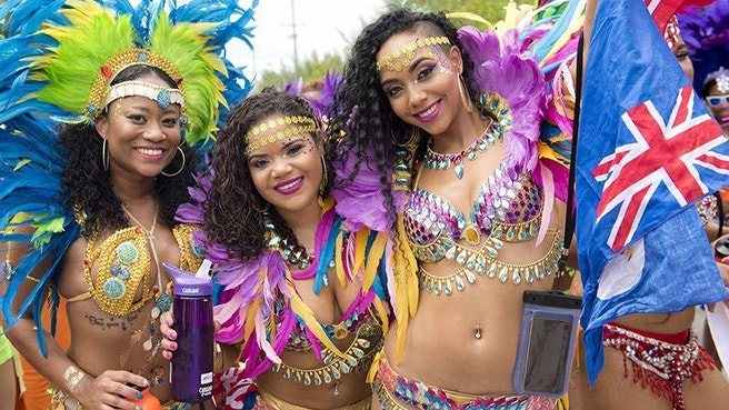 Beautiful women dressed up for carnival holding a cayman flag