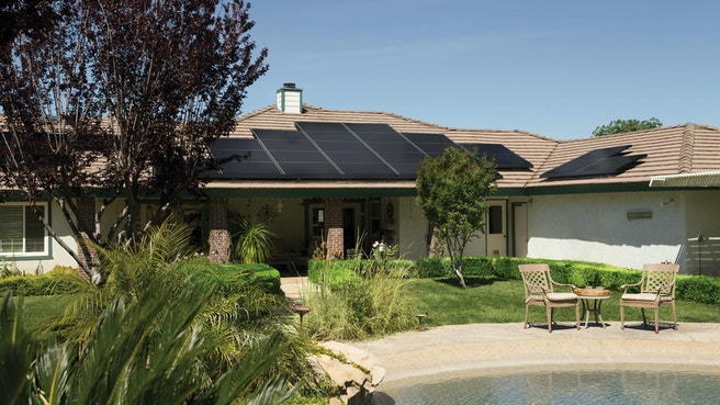 Black solar panels on brown roof of house with pool