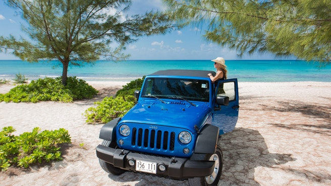 Blue jeep parked on the beach under causarina trees with woman looking at the ocean
