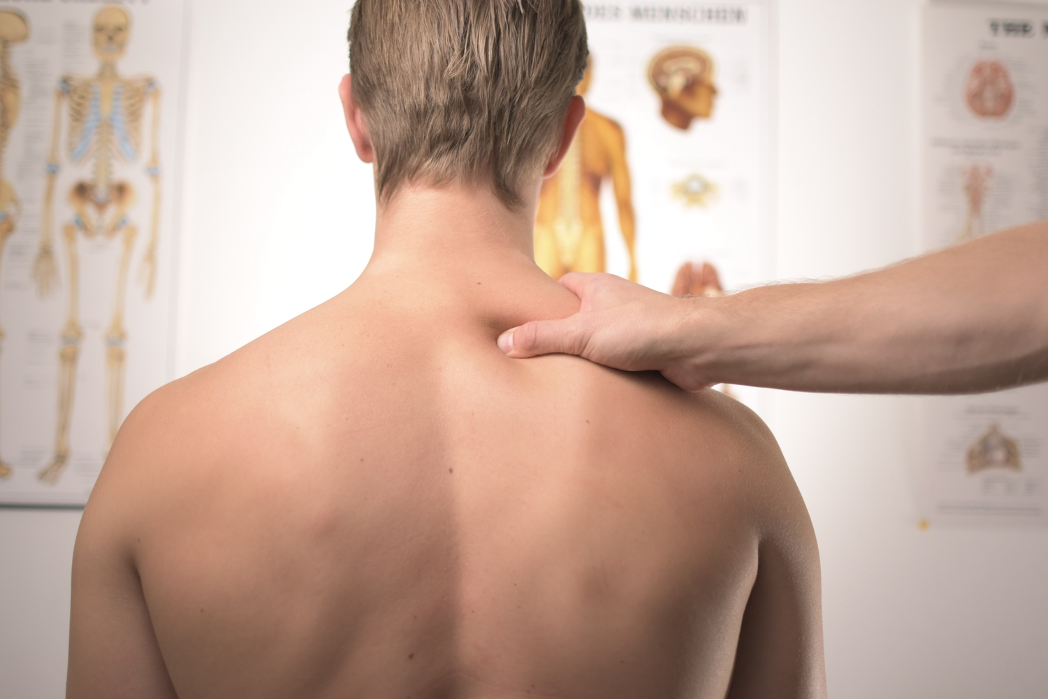 Chiropractor squeezing mans shoulder looking at charts