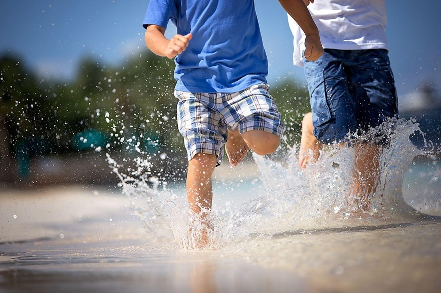 Close crop image of two little boys running through the surf