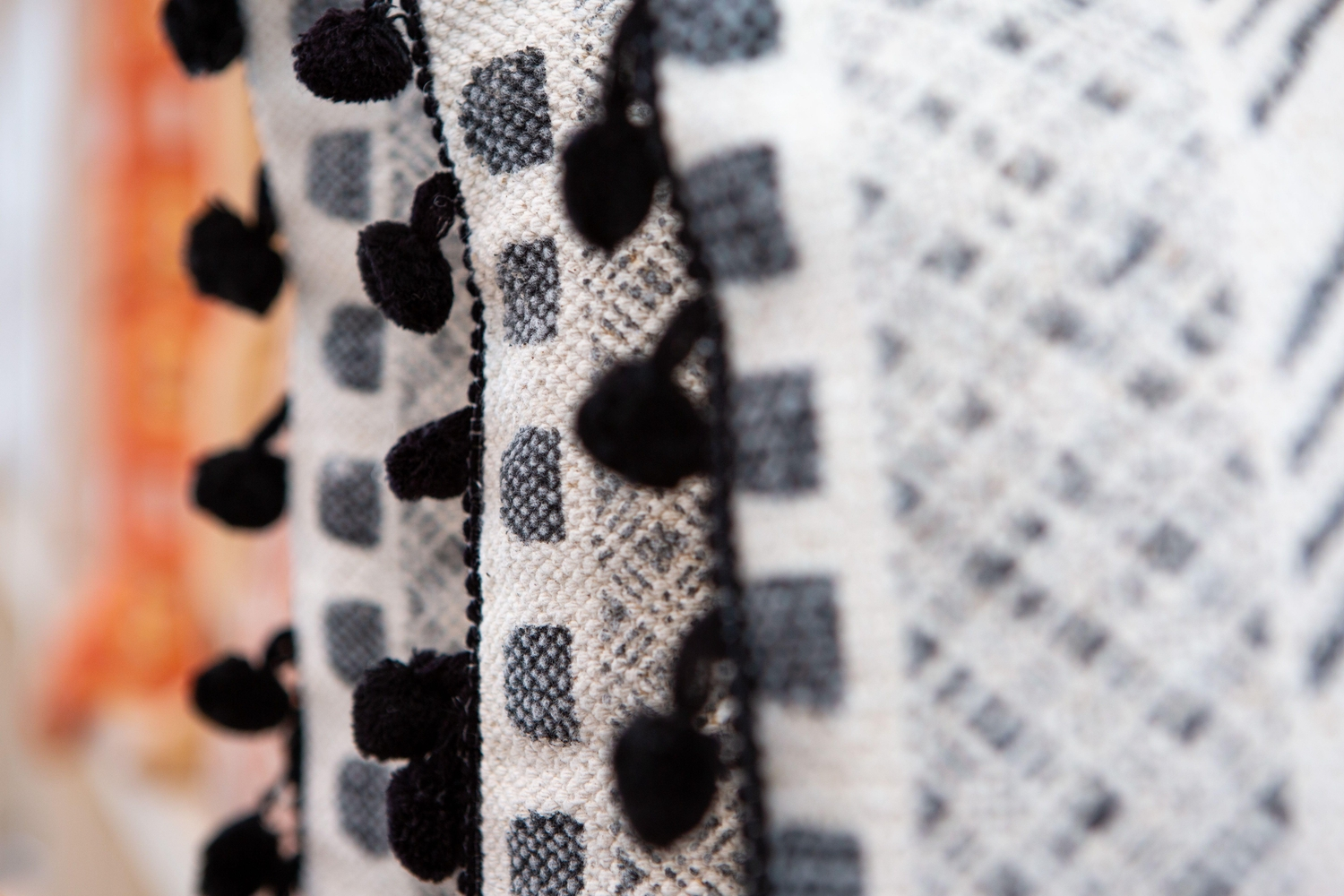 Close up of throw pillows with diffent peach and black patterns