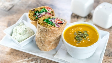 Delicious veggie wrap and soup on a white plate on an angle