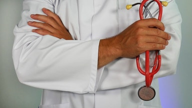 Doctor in white coat holding stethescope close up
