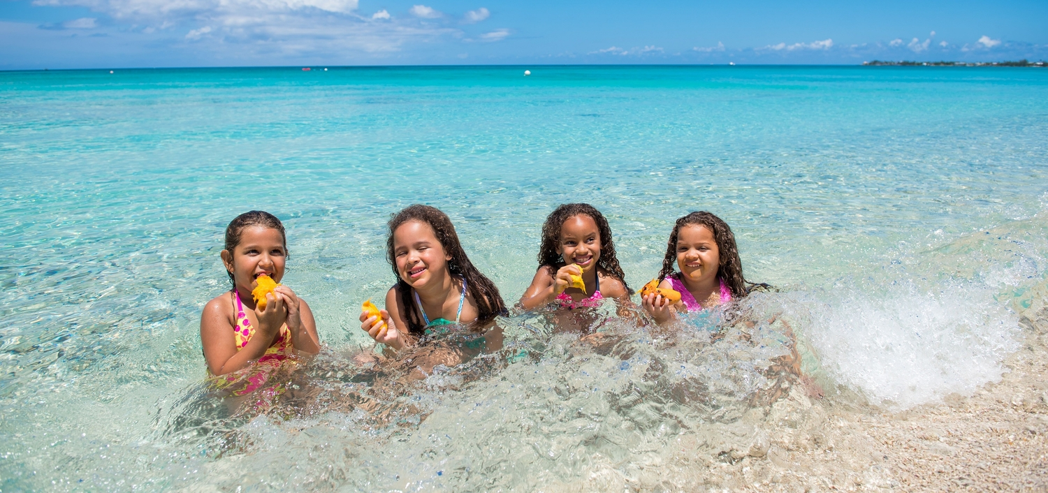 Four little girls eating mango seed in the ocean