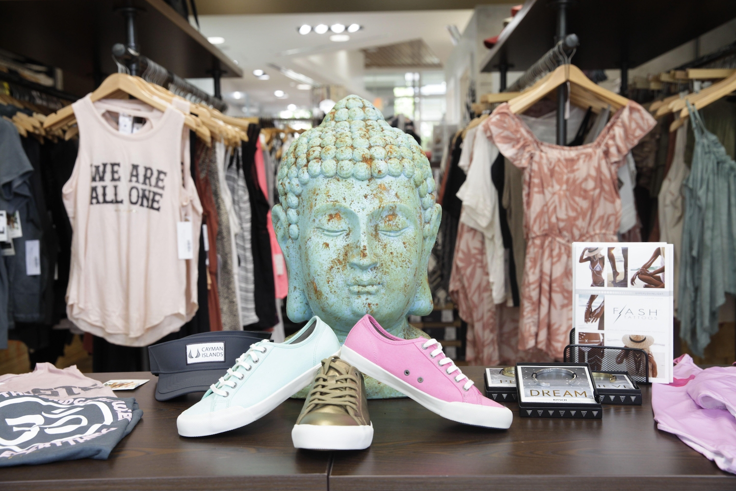 Front window display of shoes and tanks with an ornamental buddah head in the centre