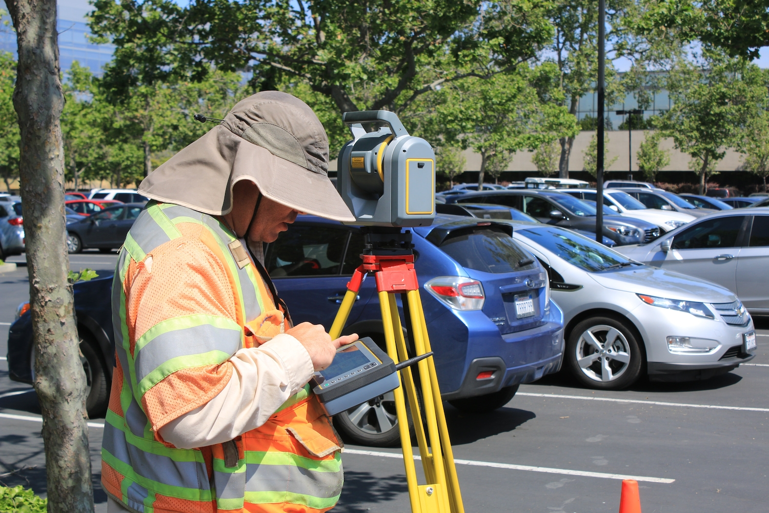 Guy in car park looking at land survey equipment