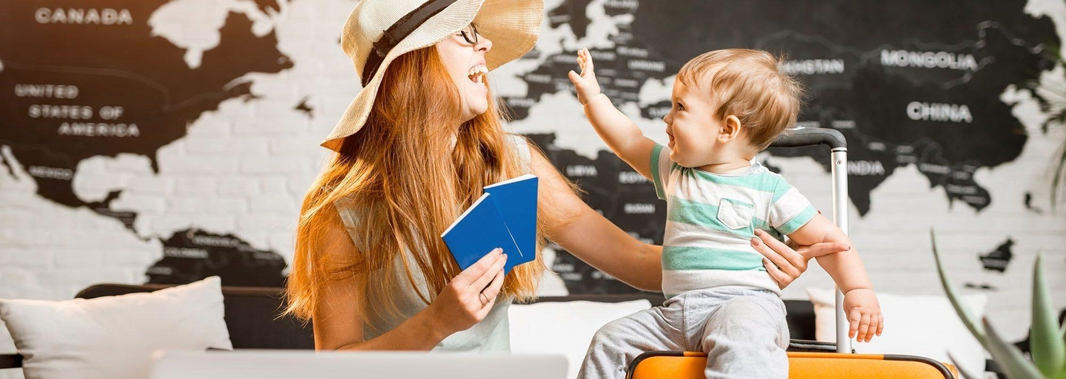 Little boy sitting on orange luggage with mother wearing hat and holding passports