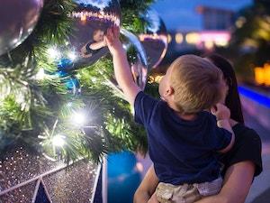 Little boy touching christmas decor on tree in camana bay