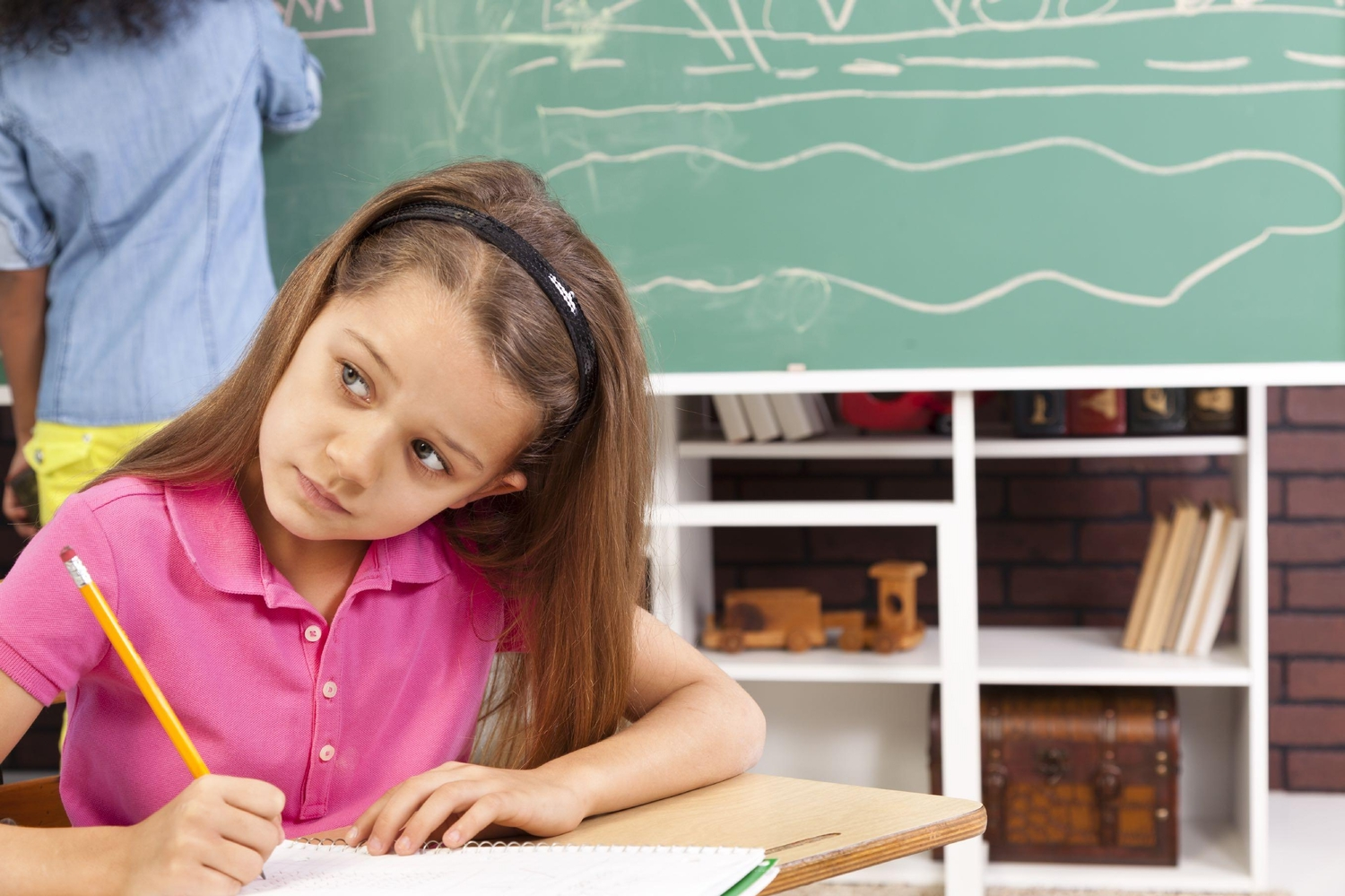 Little girl in pink collared shirt studying