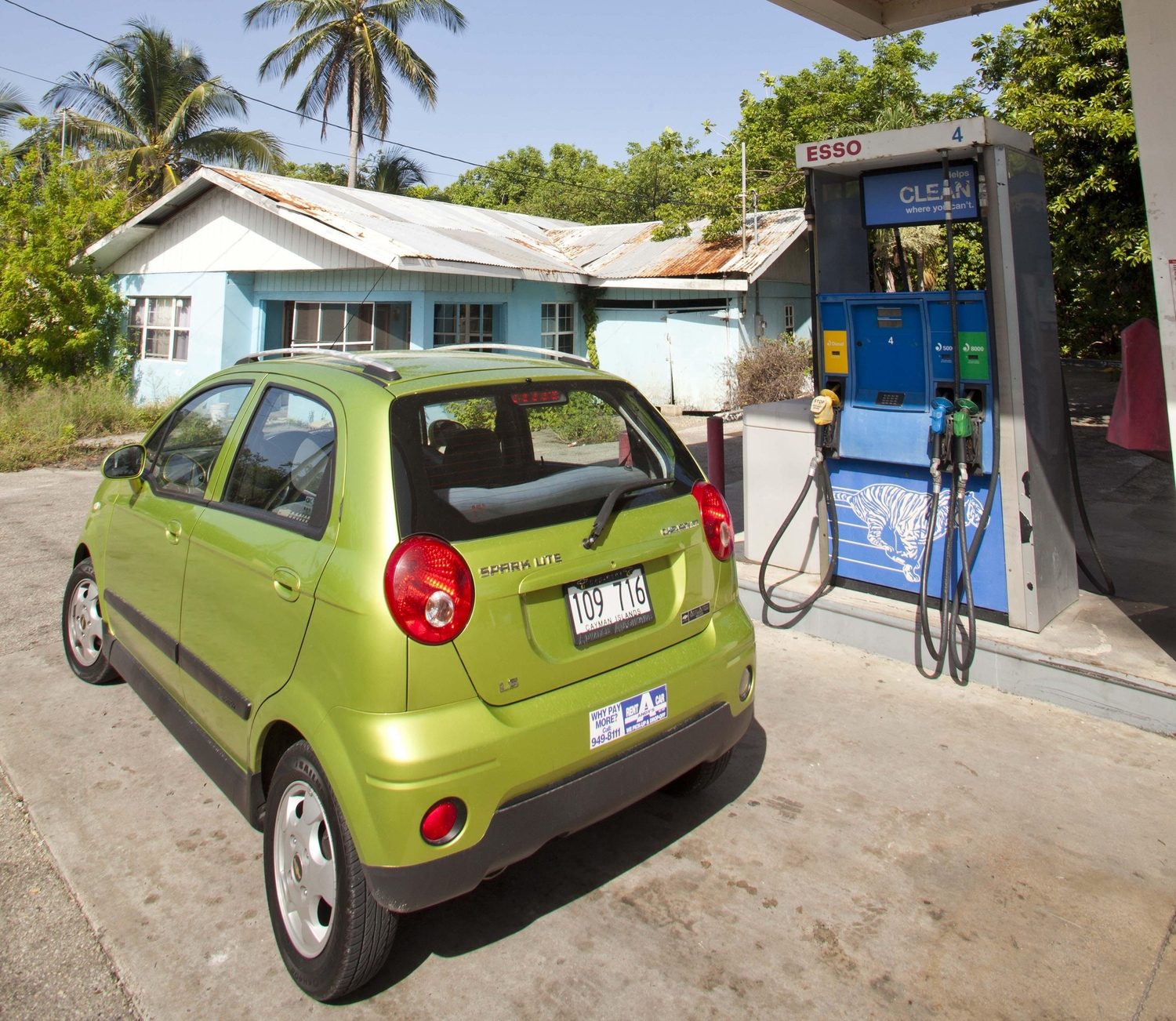 Little green car parked out from of an esso