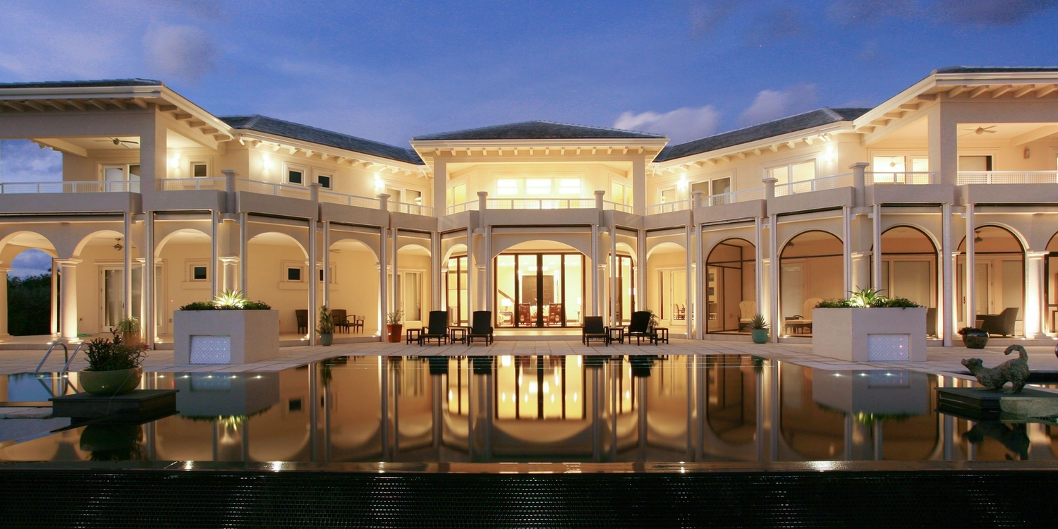 Luxury home at dusk with large infinity pool