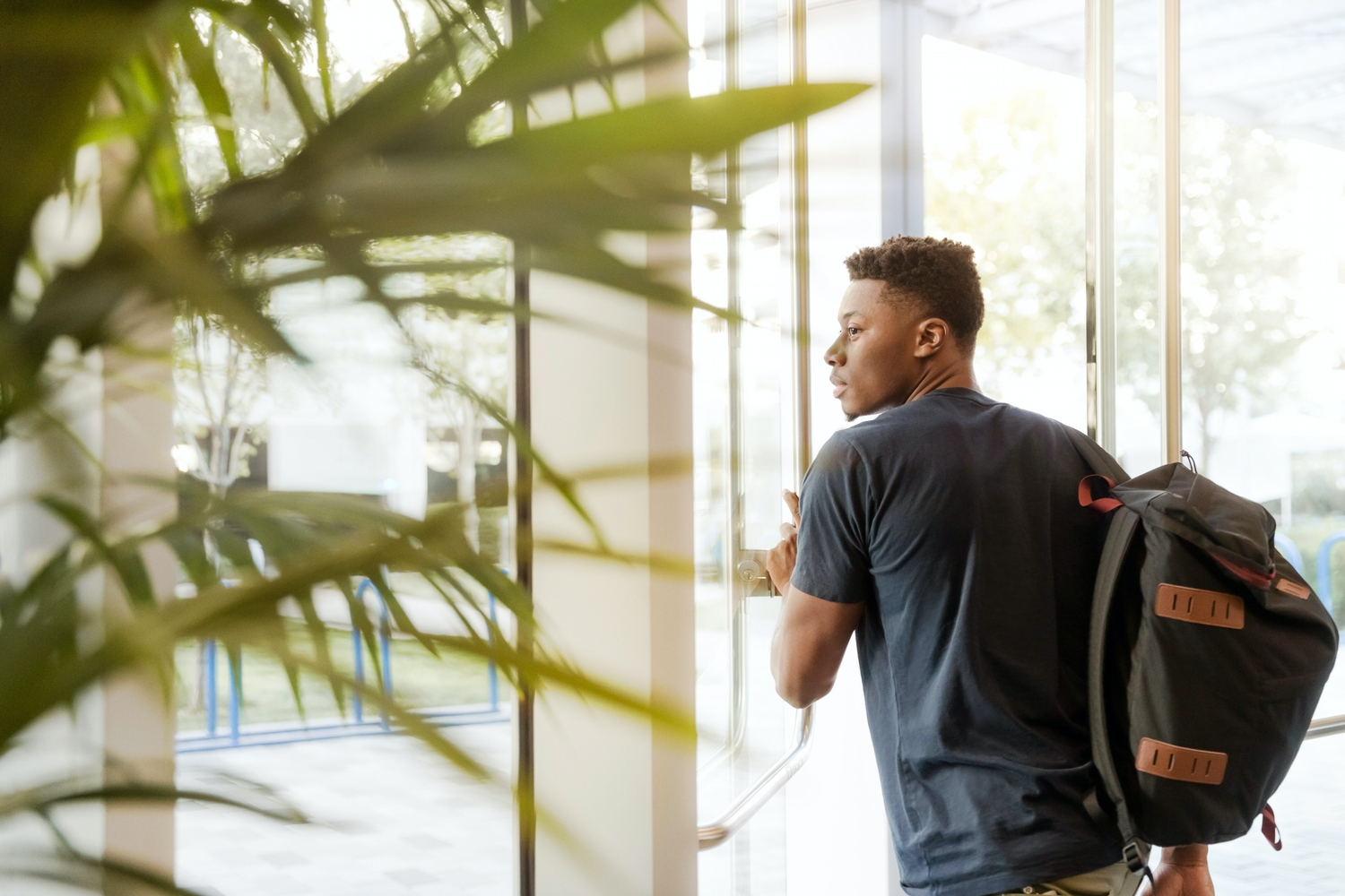 Man looking outside window carrying black and brown backpack