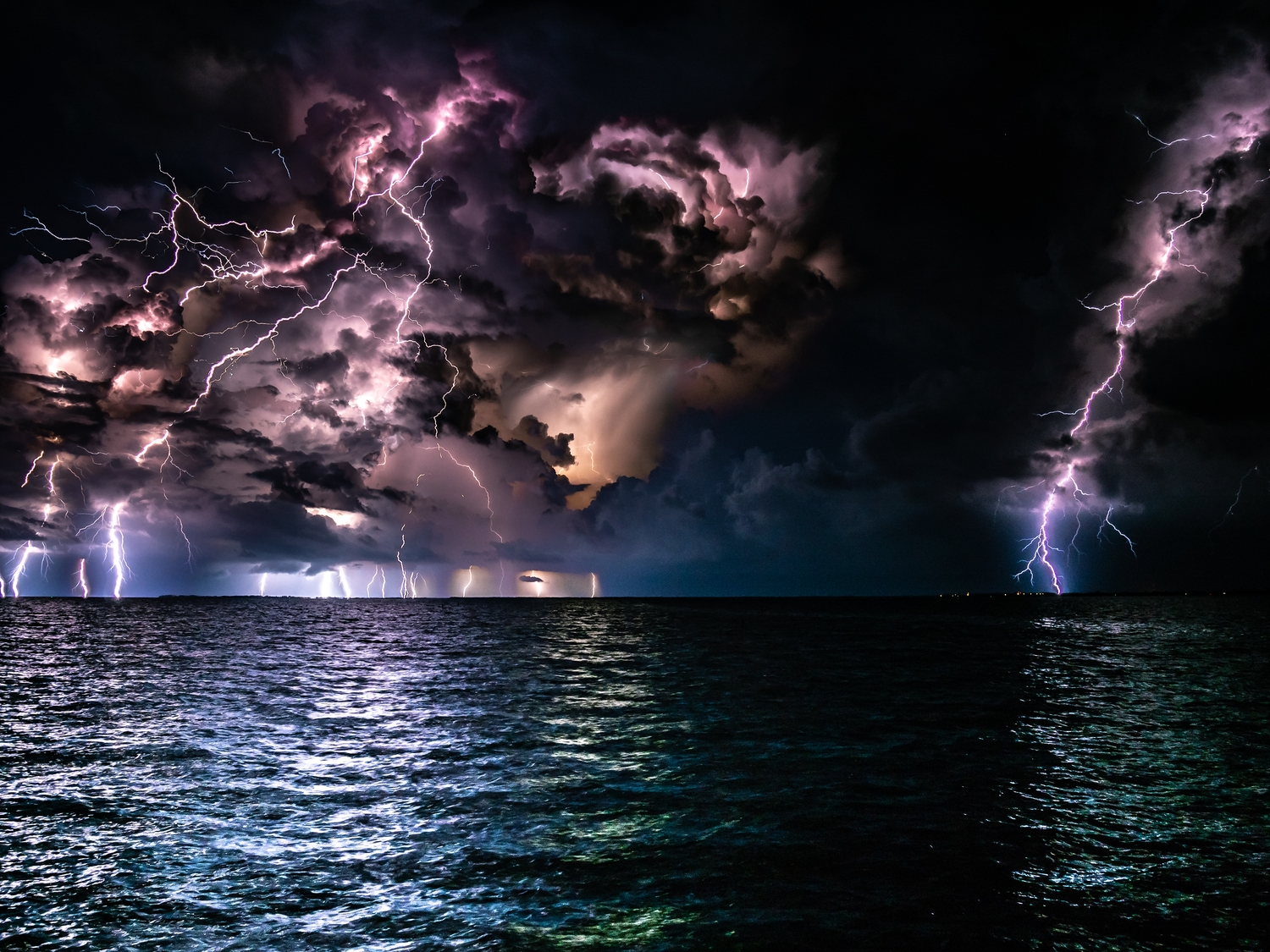 Many lightening strikes in a stormy sky overlooking the ocean