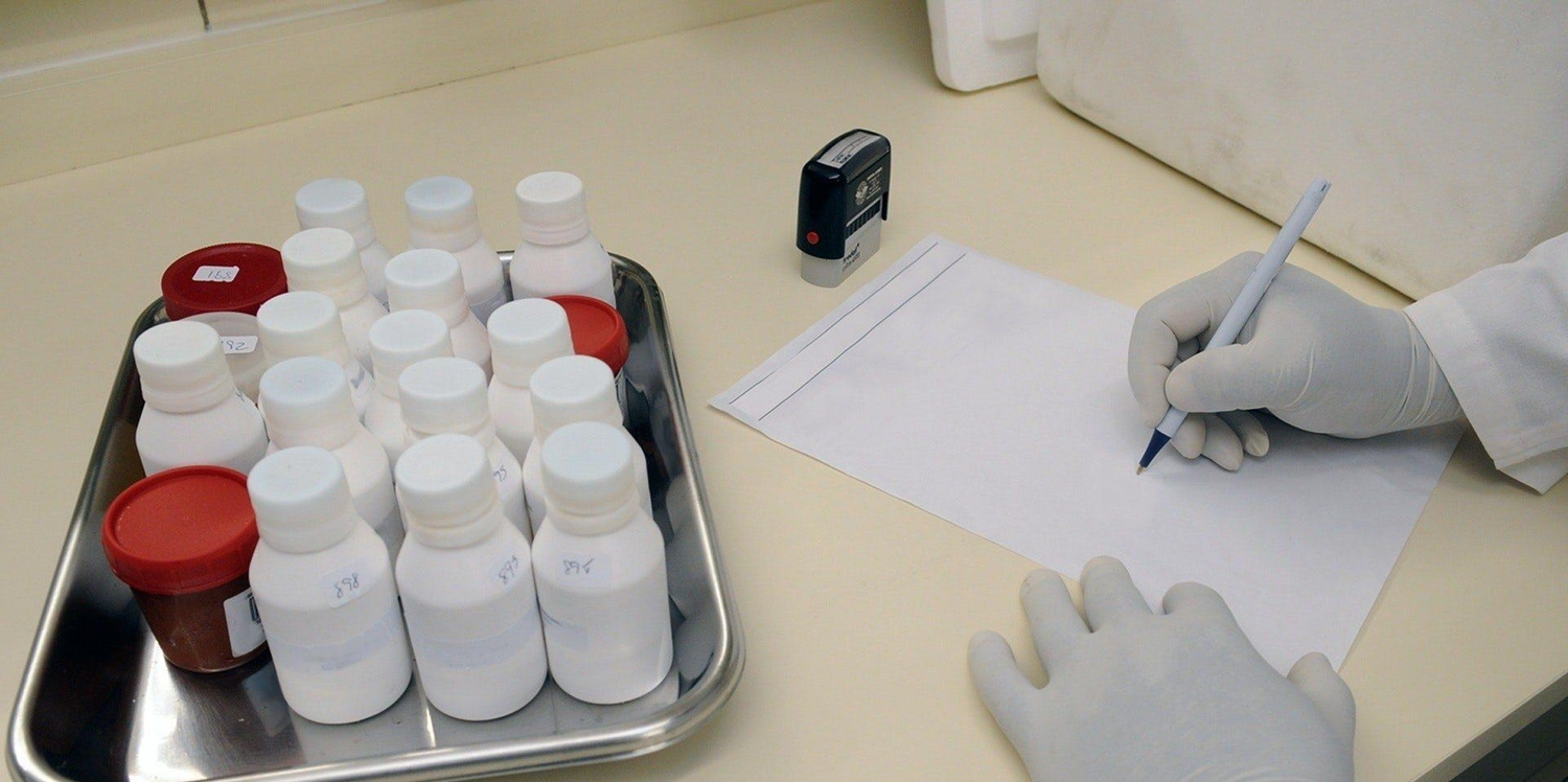 Medical samples on table and person in white hand gloves writing on white paper 207601
