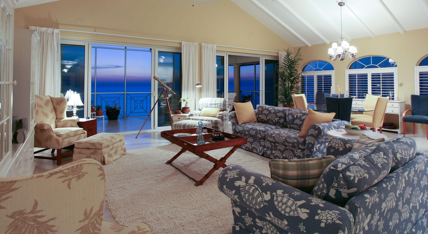 Neutral coloured tropical patterned livingroom furniture gazing over the ocean at dusk