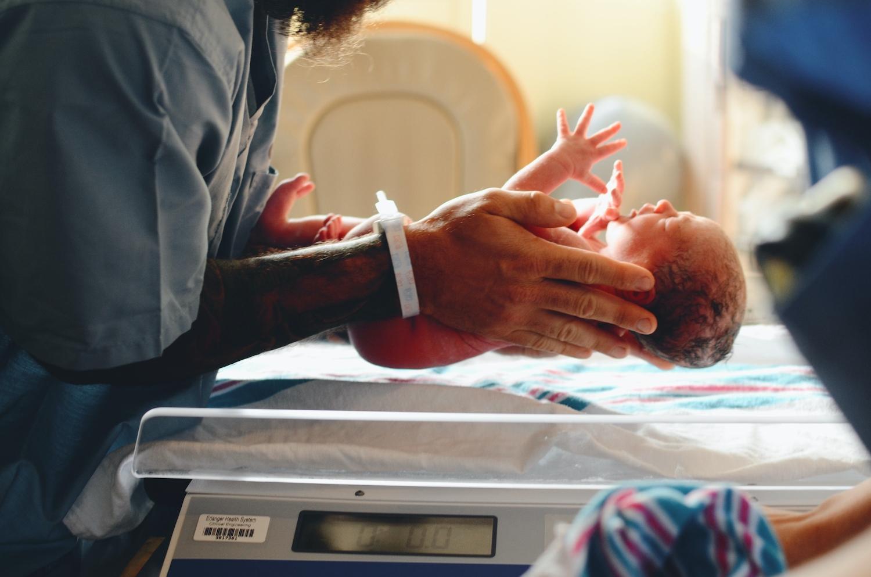 Newborn baby being weighed by a nurse