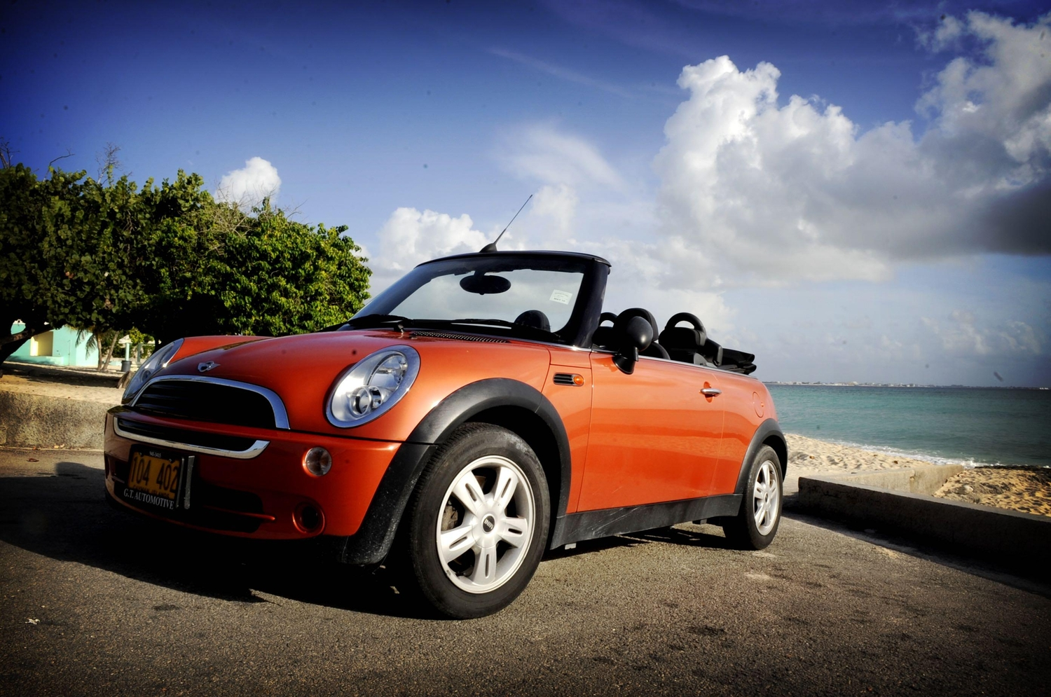 Orange mini cooper parked in front of the water